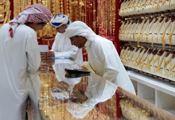 Men look at gold jewellery in a shop at the Gold Souq in Dubai